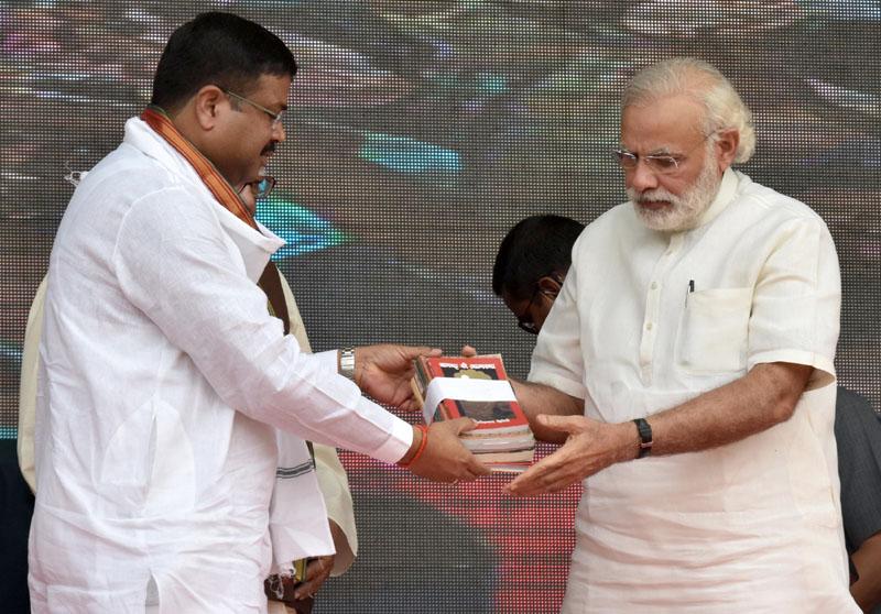 Dharmendra Pradhan offering book Narendra Modi